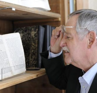 Besucher betrachtet ausgestelltes historisches Buch in der Bibliothek von Kloster Schussenried